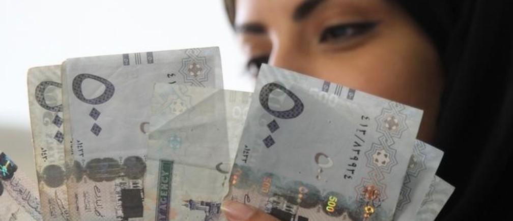 A Saudi woman poses with Saudi riyal banknotes at a money exchange shop in Riyadh, Saudi Arabia January 20, 2016. REUTERS/Faisal Al Nasser