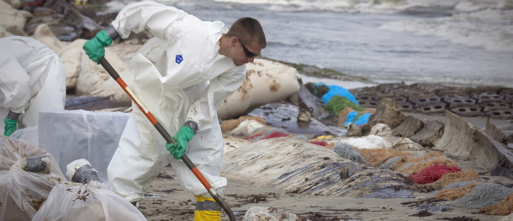 A worker contracted by British Petroleum scrapes oil from a beach after it was inundated by the oil spill from the Deepwater Horizon spill in Port Fourchon, Louisiana May 23, 2010. REUTERS/Lee Celano (UNITED STATES - Tags: DISASTER BUSINESS ENERGY) - GM1E65O0FYX01