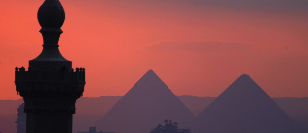 The sun sets on the minarets and the Great Pyramids of Giza (R) in Old Cairo December 31, 2013.