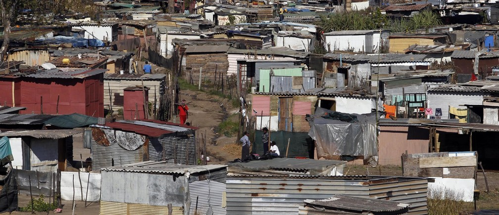 People chat in a slum in the outskirts of Johannesburg June 7, 2010. Johannesburg will host the opening ceremony and the final of the 2010 FIFA World Cup. REUTERS/Daniel Munoz (SOUTH AFRICA - Tags: CITYSCAPE SPORT SOCCER WORLD CUP SOCIETY) - GM1E6671NT301