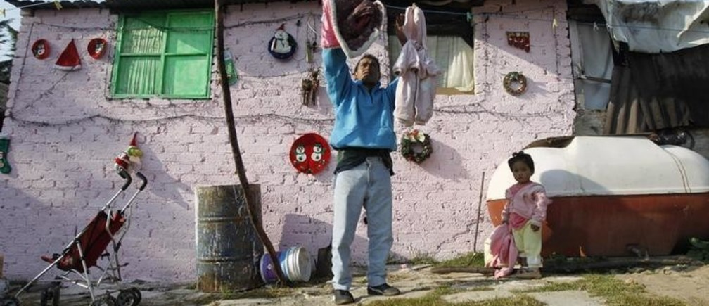 A man hangs up clothes to dry in a low-income neighborhood in Mexico City December 8, 2011. When President Felipe Calderon came to power five years ago, he pledged to cut rampant poverty in Mexico. Instead, millions more have joined the ranks of the poor and half of Mexico's population lives below the poverty line. Picture taken December 8, 2011. To match MEXICO-POVERTY/     REUTERS/Edgard Garrido (MEXICO - Tags: POLITICS SOCIETY POVERTY)