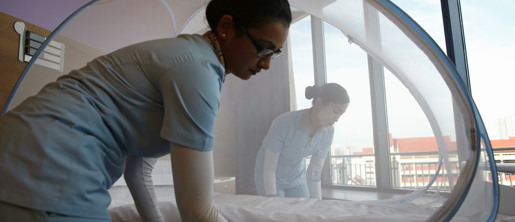 Nurses set up a mosquito tent over a hospital bed in Singapore.