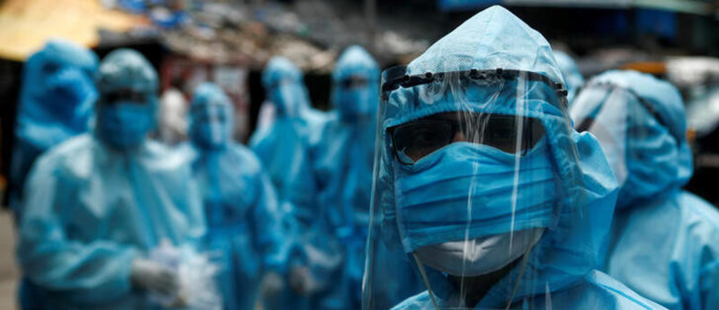 Healthcare workers wait to take off their personal protective equipment (PPE) after the end of a check-up camp for the coronavirus disease (COVID-19) at a slum in Mumbai, India June 14, 2020. REUTERS/Francis Mascarenhas