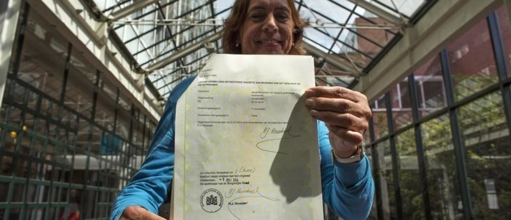 Petra van Dijk, 51, displays her new documents after changing her officially registered gender from male to female, in the City Hall in Amsterdam July 1, 2014. Dijk is among the first to obtain new documents on Tuesday, when a new law came into effect, legalising the registration of a transgender person's preferred gender in official state documents, including identity cards and passports. It eliminates the previous law, which required hormonal treatment, surgery or sterilization before any change in gender registration is allowed.