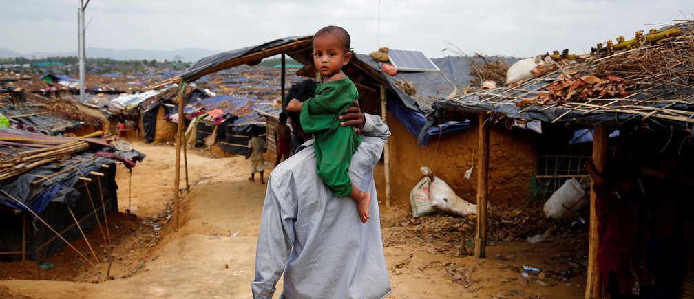 A Rohingya refugee man walks on as he carries a child on his shoulder at the Kutupalang Makeshift Refugee Camp in Cox's Bazar, Bangladesh, June 1, 2017. REUTERS/Mohammad Ponir Hossain - RTX38IMU