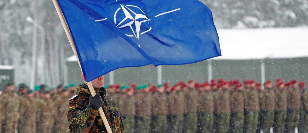 A soldier carries the NATO flag during German Minister of Defence Ursula von der Leyen's visit to German troops deployed as part of NATO enhanced Forward Presence (eFP) battle group in Rukla military base, Lithuania February 4, 2019. REUTERS/Ints Kalnins - RC1587B67C10