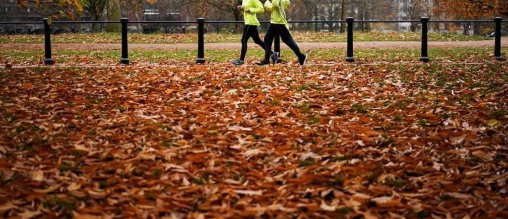 People jog through Hyde Park during autumnal weather in London, Britain, November 23, 2019. REUTERS/Henry Nicholls - RC23HD9SSDJL