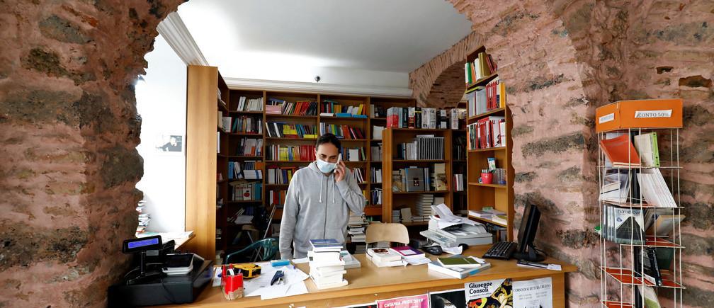 Un vendeur portant un masque facial se tient dans un magasin alors que le gouvernement italien autorise la réouverture de certains magasins alors que le verrouillage se poursuit à l'échelle nationale, suite à l'apparition d'une maladie à coronavirus (COVID-19) à Catane, en Italie, le 14 avril 2020.