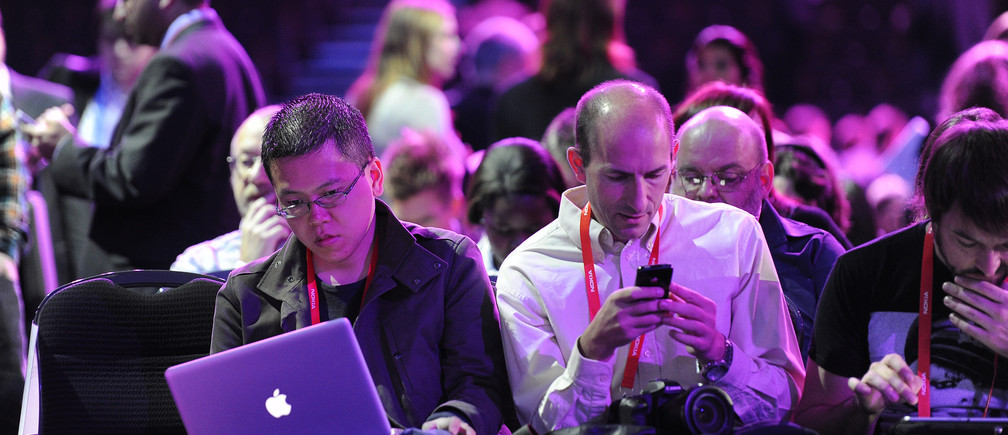 People attending the Nokia World event check their laptops and mobile devices in London October 26, 2011.