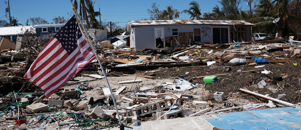 A U.S. flag flies over a debris field of former houses following Hurricane Irma in Islamorada, Florida, U.S., September 15, 2017. REUTERS/Carlo Allegri - RC18DD9EFA30