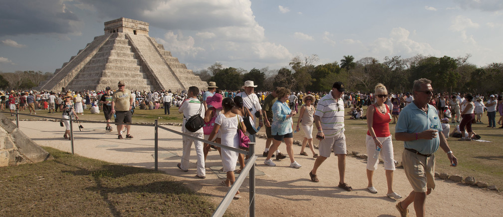 Tourists walk near the Castle of Kukulcan, one of the seven wonders of the modern world, at the archaeological site of Chichen Itza during the spring equinox, on the Yucatan Peninsula March 21, 2013.