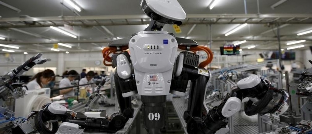 A humanoid robot works side by side with employees in the assembly line at a factory of Glory Ltd., a manufacturer of automatic change dispensers, in Kazo, north of Tokyo, Japan, July 1, 2015. Japanese firms are ramping up spending on robotics and automation, responding at last to premier Shinzo Abe's efforts to stimulate the economy and end two decades of stagnation and deflation. Picture taken July 1, 2015.