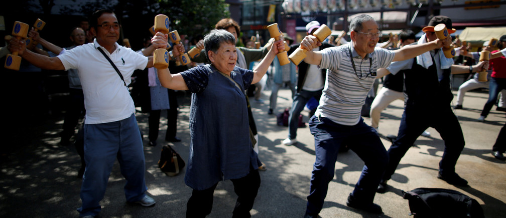 "Participants including elderly and middle-aged people exercise with wooden dumbbells during a health promotion event to mark Japan's ""Respect for the Aged Day"" at a temple in Tokyo's Sugamo district, an area popular among the Japanese elderly, September 17, 2018. REUTERS/Issei Kato      TPX IMAGES OF THE DAY - RC14EDF2A330"