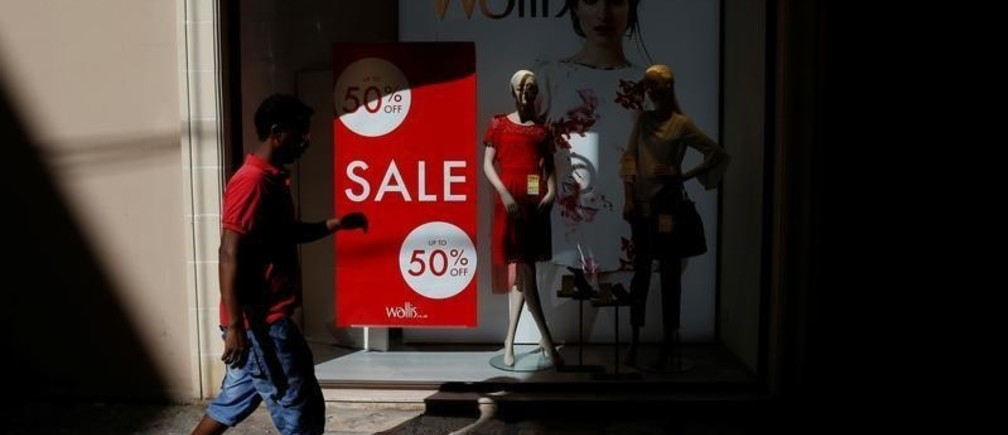 An African migrant walks past a Wallis clothing store shop window advertising a sale in Valletta, Malta, July 31, 2017.   REUTERS/Darrin Zammit Lupi - RC14A452BEA0
