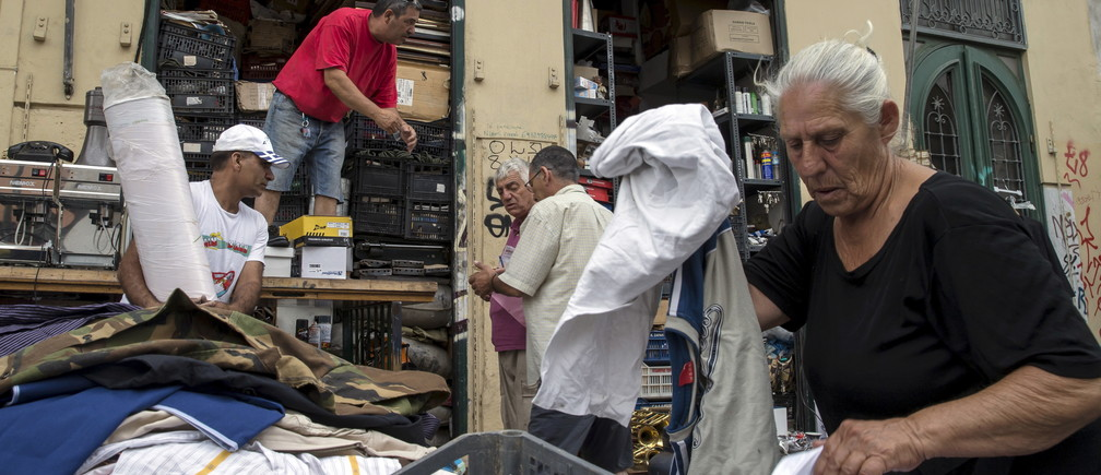 "People prepare their stuff for sale at a flea market in Athens, Greece, June 22, 2015. The European Union welcomed new proposals from Greek Prime Minister Alexis Tsipras as a ""good basis for progress"" at talks on Monday where creditors want 11th-hour concessions to haul Athens back from the brink of bankruptcy. REUTERS/Marko Djurica - GF10000135655"