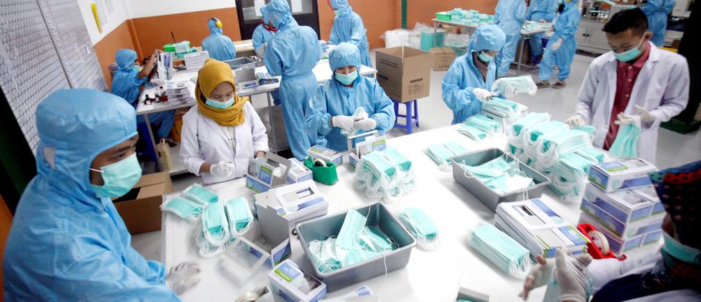 Empleados del personal hacen una mascarilla protectora en una fábrica, en medio del brote de la enfermedad coronavirus (COVID-19) en Gunung Putri, Bogor, cerca de Yakarta el 15 de abril de 2020