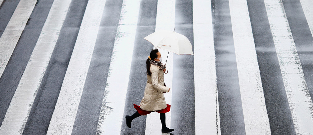 A woman wearing a protective face mask, following an outbreak of the coronavirus disease (COVID-19), runs on a street near Tamachi station in Tokyo, Japan March 8, 2020. REUTERS/Edgard Garrido - RC2OFF9NJ58S