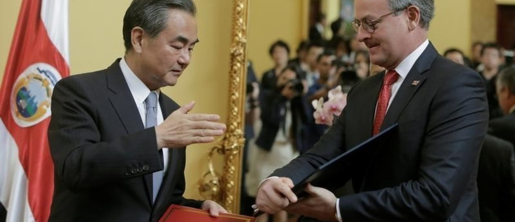 China's Foreign Minister Wang Yi (L) and Costa Rica's Foreign Minister Manuel Gonzalez exchange documents after signing a joint agreement at the foreign ministry in San Jose, Costa Rica September 15, 2017.