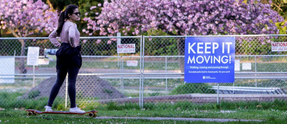 A woman rides a longboard past a sign at Seaward Park telling people to keep moving after Seattle Mayor Jenny Durkan reopened parks that were closed Easter weekend as efforts continue to help slow the spread of the coronavirus disease (COVID-19) in Seattle, Washington, U.S. April 19, 2020.  REUTERS/Jason Redmond - RC248G9M1G2C