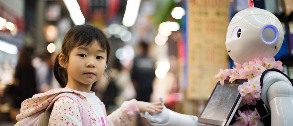 A girl makes a robot friend at Kuromon Ichiba market, Osaka, Japan