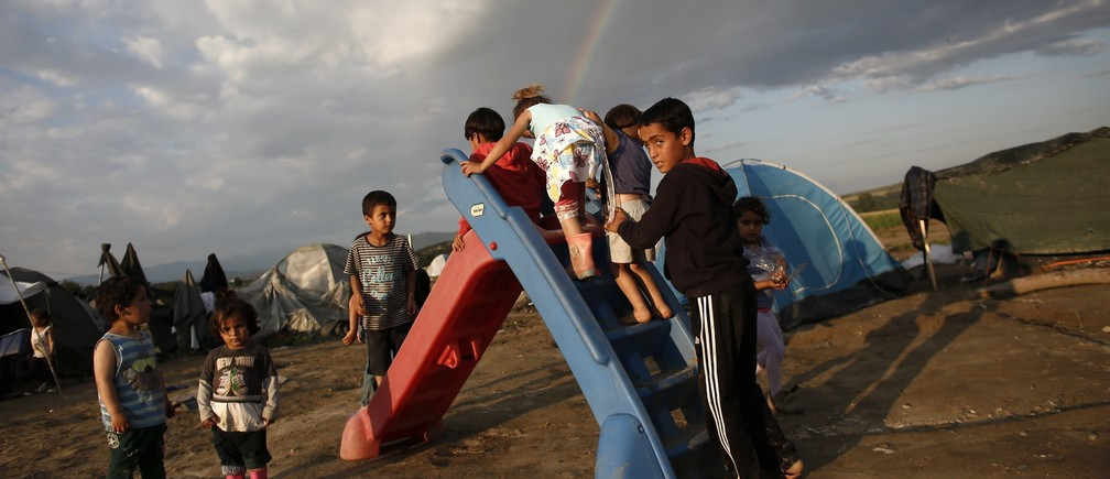 Children play on a slide as a rainbow forms overhead at a makeshift camp for refugees and migrants at the Greek-Macedonian border near the village of Idomeni, Greece, May 22, 2016.