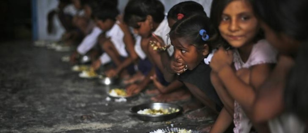 School children eat their free mid-day meal, distributed by a government-run primary school, at Brahimpur village in Chapra district of the eastern Indian state of Bihar July 19, 2013. Police suspect that India's worst outbreak of mass food poisoning in years was caused by cooking oil that had been kept in a container previously used to store pesticide, the magistrate overseeing the investigation said on Friday. REUTERS/Adnan Abidi (INDIA - Tags: DISASTER HEALTH FOOD EDUCATION TPX IMAGES OF THE DAY)