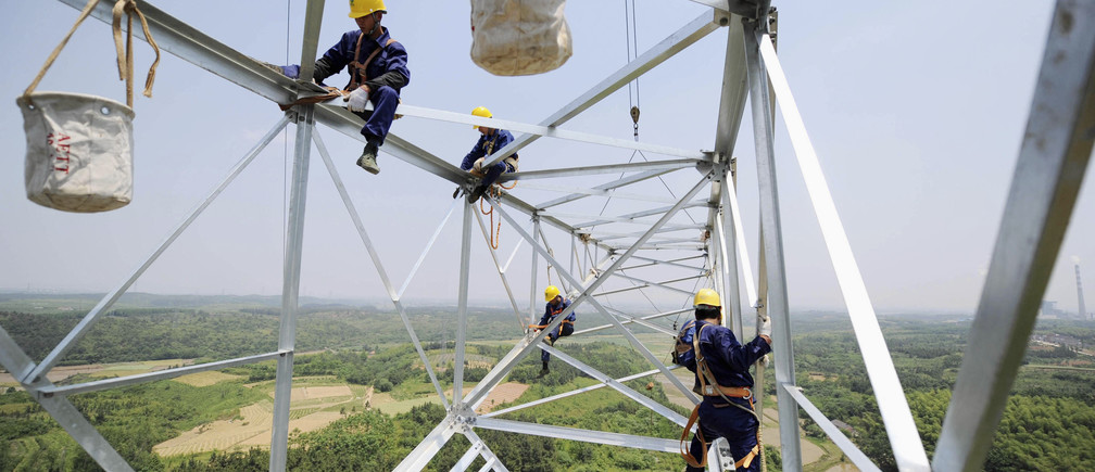Workers install a high voltage electricity pylon in Xuancheng, Anhui province, May 17, 2011