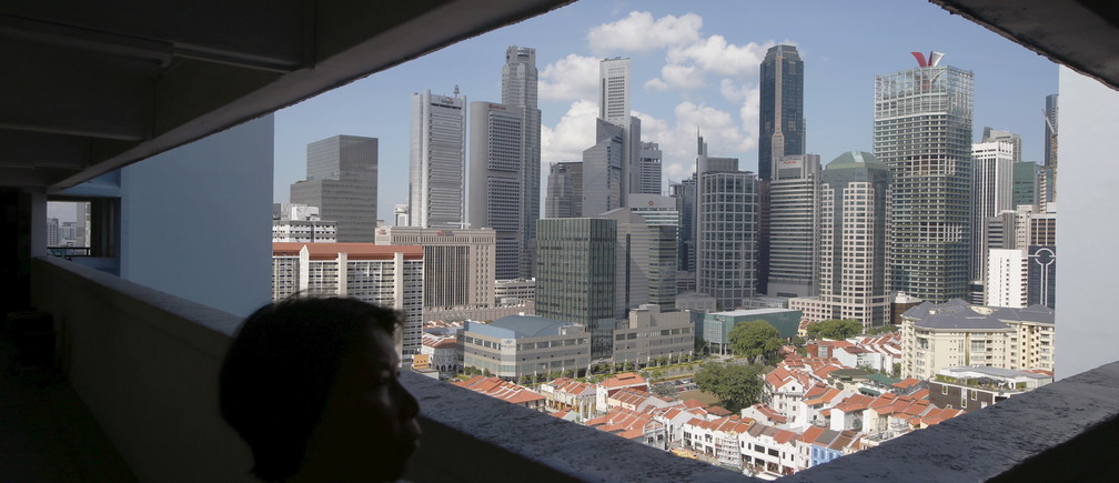 A woman passes the skyline of the central business district, in a public housing estate in Singapore, April 14, 2015. Singapore's central bank on Tuesday surprised markets by holding them off from further monetary easing, saying an improved outlook for global growth would underpin the trade-reliant economy