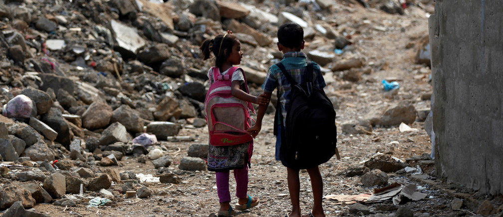 A boy and girl walk along rubble of a damaged house as they head to school in a slum in Karachi, Pakistan July 20, 2017.