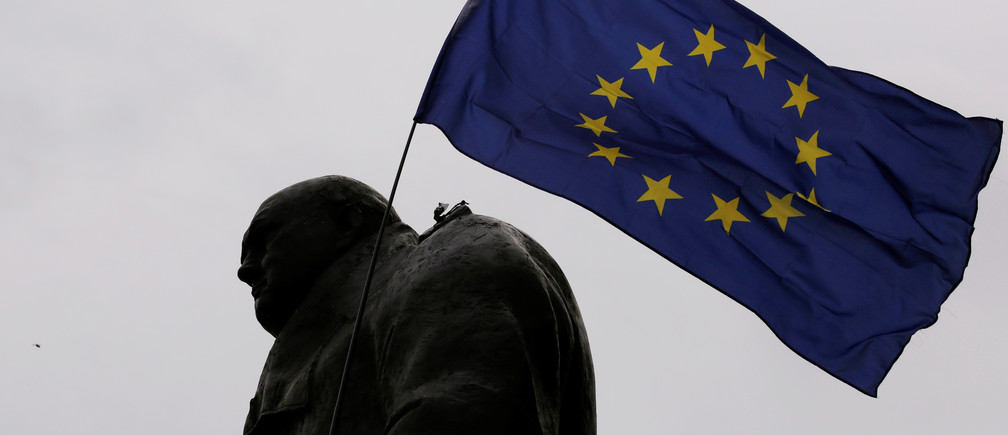 "A European Union flag is waved over a statue of former Prime Minister Winston Churchill as demonstrators protest during a ""March for Europe"" against the Brexit vote result earlier in the year, in London, Britain, September 3, 2016."