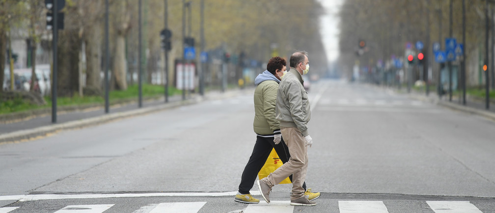 People walk in an empty street, during a lockdown against the spread of coronavirus disease (COVID-19) in Milan, Italy March 22, 2020. REUTERS/Daniele Mascolo - RC2ZOF9RNG6L