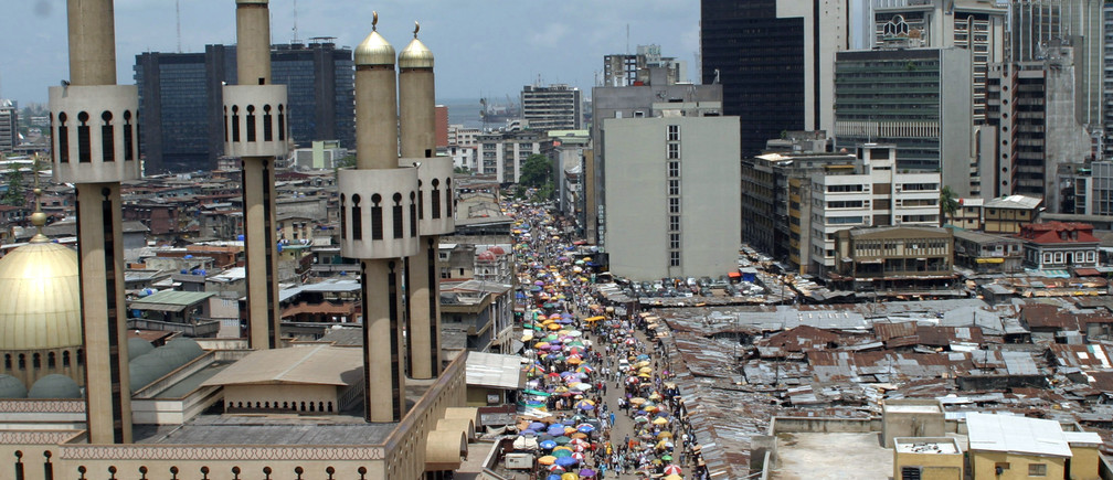 People and traffic move along a busy street in Lagos, Nigeria.