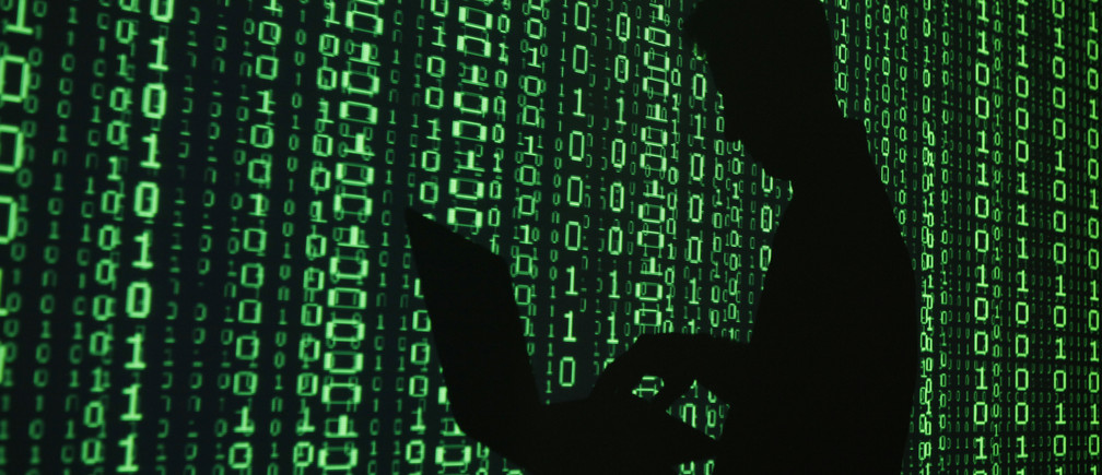 An illustration picture shows a projection of binary code on a man holding a laptop computer