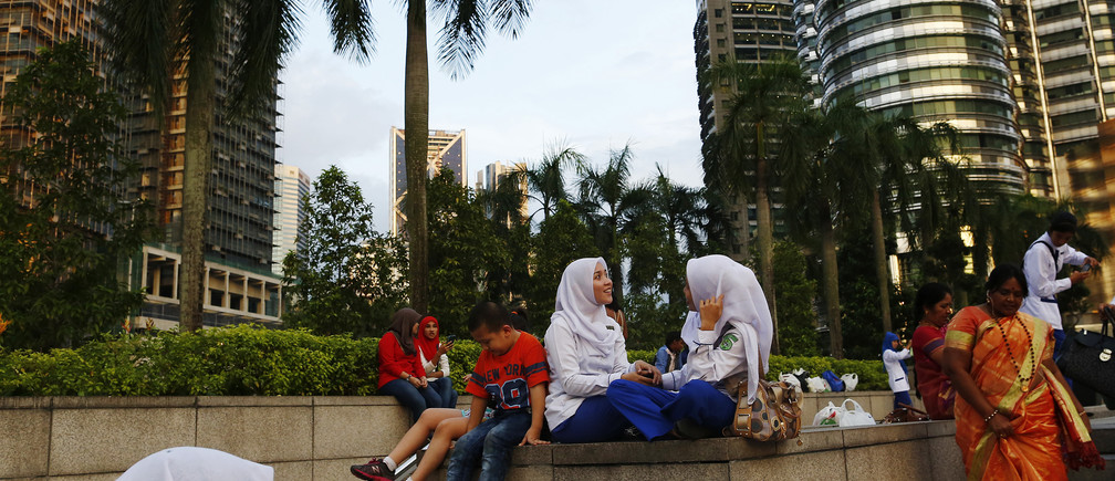 Women talk in front of the Petronas towers in Kuala Lumpur December 10, 2014.