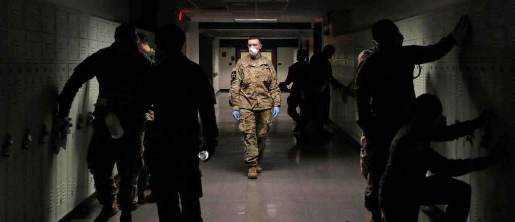 Les membres de la Task Force 2, composée de soldats et d'aviateurs de l'armée et de la garde nationale aérienne de New York, travaillent à l'assainissement du lycée de New Rochelle lors de l'épidémie de coronavirus (COVID-19) qui s'est produite à New Rochelle, New York, États-Unis, le 21 mars 2020.