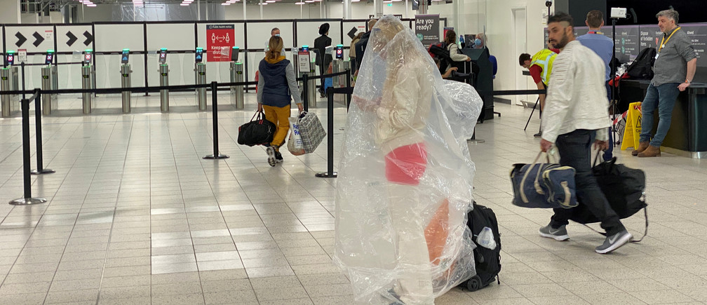 A passenger covered with a plastic bag is seen at Luton Airport, following the outbreak of the coronavirus disease (COVID-19), Luton, Britain, June 4, 2020. REUTERS/Paul Childs     TPX IMAGES OF THE DAY - RC2B2H93QR0M