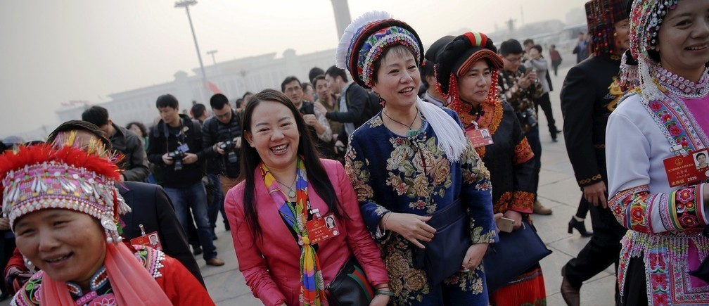 Ethnic minority delegates laugh as they arrive for the closing ceremony of China's National People's Congress (NPC) at the Great Hall of the People in Beijing, China.