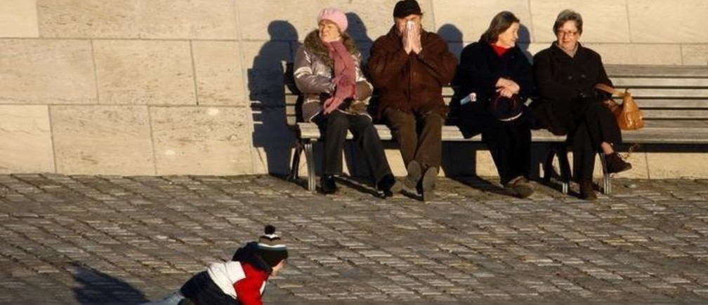 A boy enjoys the sun on a skateboard while elderly people sit on a bench in Berlin January 13, 2008. REUTERS/Johannes Eisele (GERMANY)