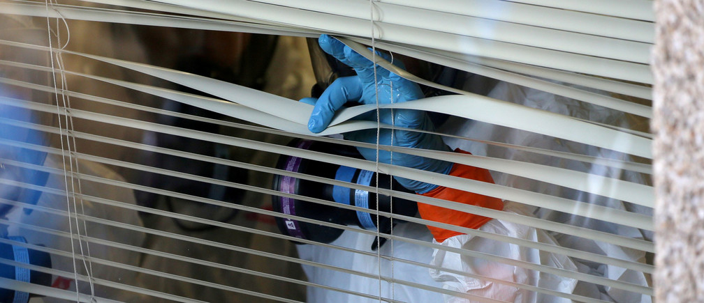 A person peers through the blinds from inside the Life Care Center of Kirkland, the long-term care facility linked to several confirmed coronavirus cases in the state, in Kirkland, Washington, U.S. March 11, 2020.  REUTERS/Karen Ducey