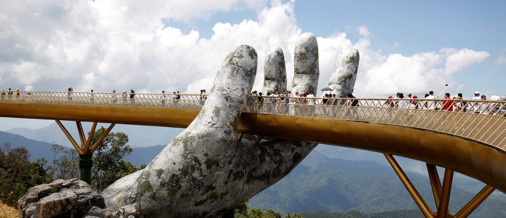Tourists walk past giant hand structure on the Gold Bridge on Ba Na hill near Danang City, Vietnam August 1, 2018. REUTERS/Kham TPX IMAGES OF THE DAY - RC1474B0A670