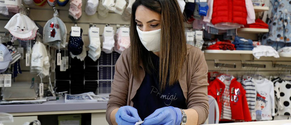 A vendor wearing a face mask works inside the store as the Italian government allows the reopening of some shops while a nationwide lockdown continues, following the outbreak of coronavirus disease (COVID-19) in Catania, Italy, on 14 April 2020.