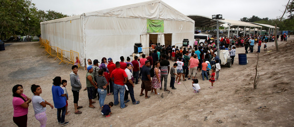 Migrants seeking asylum in the U.S. queue for food at an encampment of more than 2,000 migrants, as local authorities prepare to respond to the coronavirus disease (COVID-19) outbreak, in Matamoros, Mexico March 20, 2020. Picture taken March 20, 2020. REUTERS/Daniel Becerril - RC26PF9XXVHU