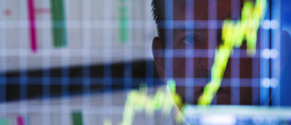 A finance trader looks up at a chart on his computer screen.