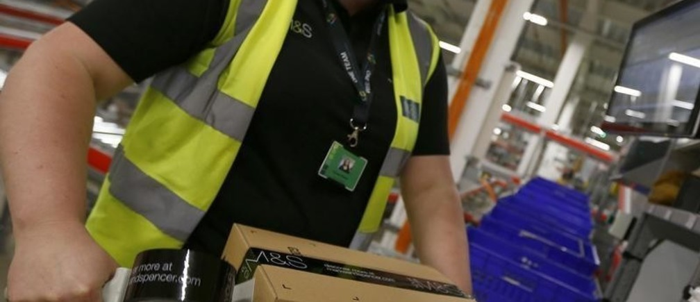 A worker boxes goods at the new Marks & Spencer e-commerce distribution centre in Castle Donington, central England May 8, 2013. The company was updating on its supply chain and IT investment programme, on Wednesday, to the media and to investors.