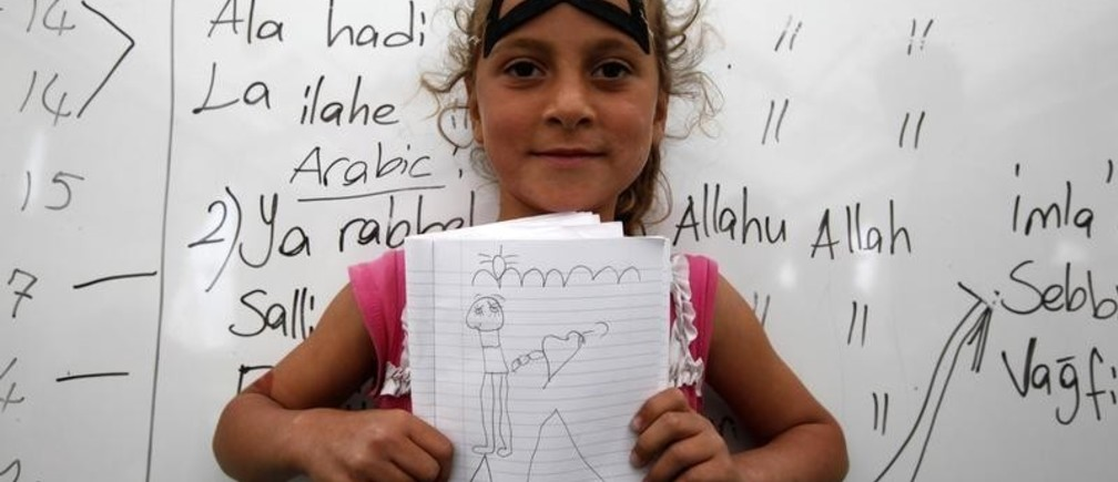 Meriya Senkar, 10, a Syrian refugee, shows a drawing of her dream home during a class at a school for refugee children at Boynuyogun refugee camp in Hatay province near the Turkish-Syrian border April 11, 2012.