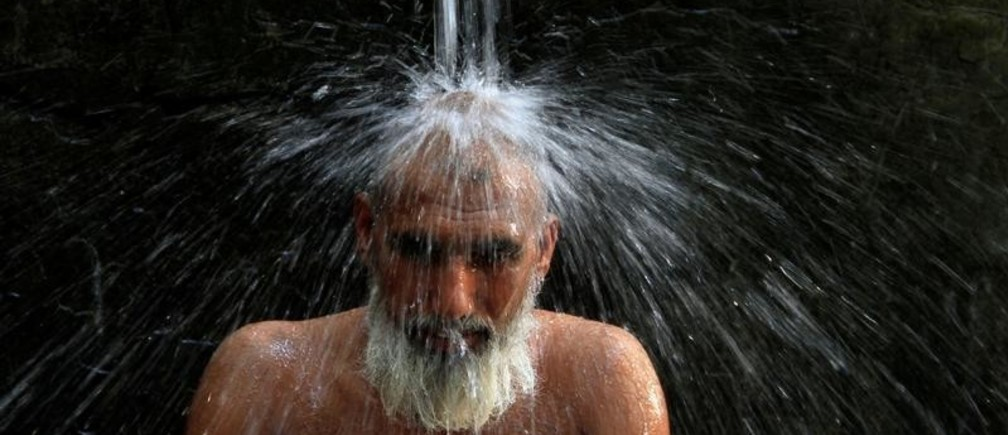 A man cools off from the heatwave, as he takes a shower at a public bath in Lahore, Pakistan May 27, 2018. REUTERS/Mohsin Raza - RC186E65B8A0