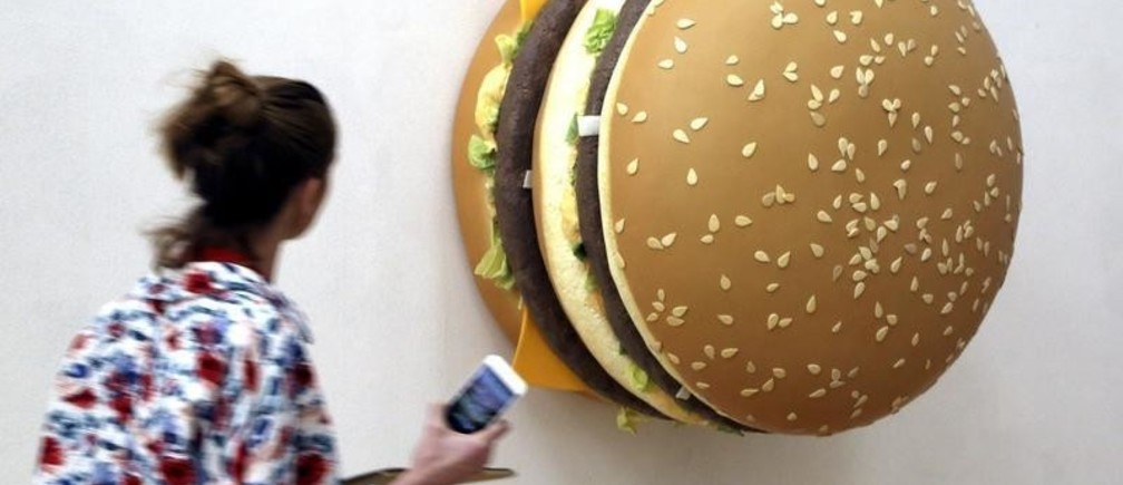 """A woman looks at a creation by Tom Friedman named 'Big Big Mac' during the unveiling of the Arts & Food exhibition at the Triennale, as part of the next Expo 2015, in downtown Milan April 8, 2015. The theme of this year's expo is """"Feeding the Planet, Energy for Life"""", and it will run from May 1 to October 31, 2015.   REUTERS/Stefano Rellandini - GF10000052572"""