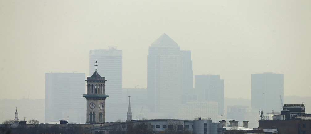 Smog surrounds the Canary Wharf financial district in London April 3, 2014. A dust cloud from the Sahara has covered south east England, raising pollution levels to the highest level in London, preventing people taking exercise outdoors, including the Prime Minister, David Cameron, who said he had skipped his morning jog. REUTERS/Suzanne Plunkett (BRITAIN - Tags: ENVIRONMENT CITYSCAPE) - LM1EA43184G01