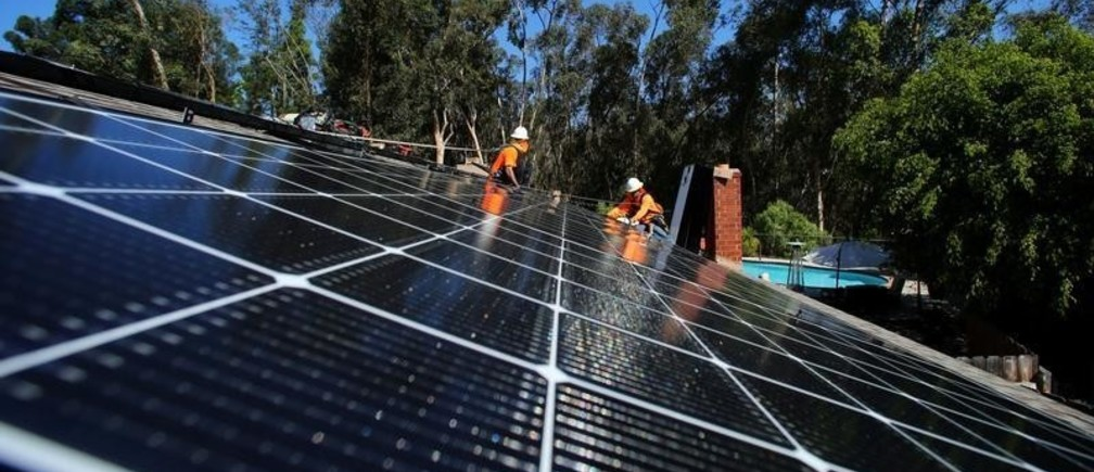 Solar installers from Baker Electric place solar panels on the roof of a residential home in Scripps Ranch, San Diego, California, U.S. October 14, 2016.  Picture taken October 14, 2016.      REUTERS/Mike Blake - S1AEUJDNMAAC