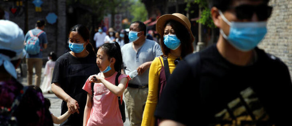 People wearing face masks visit Gubei Water Town on the first day of the five-day Labour Day holiday, following the coronavirus disease (COVID-19) outbreak, on the outskirts of Beijing, China, May 1, 2020. REUTERS/Carlos Garcia Rawlins